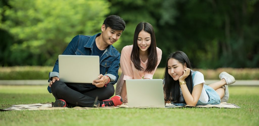 Photo of young people in a park using laptop computers